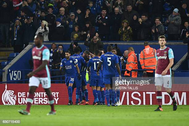 Leicester City's Algerian striker Islam Slimani is mobbed by teammates as he celebrates scoring his team's first goal during the English Premier...