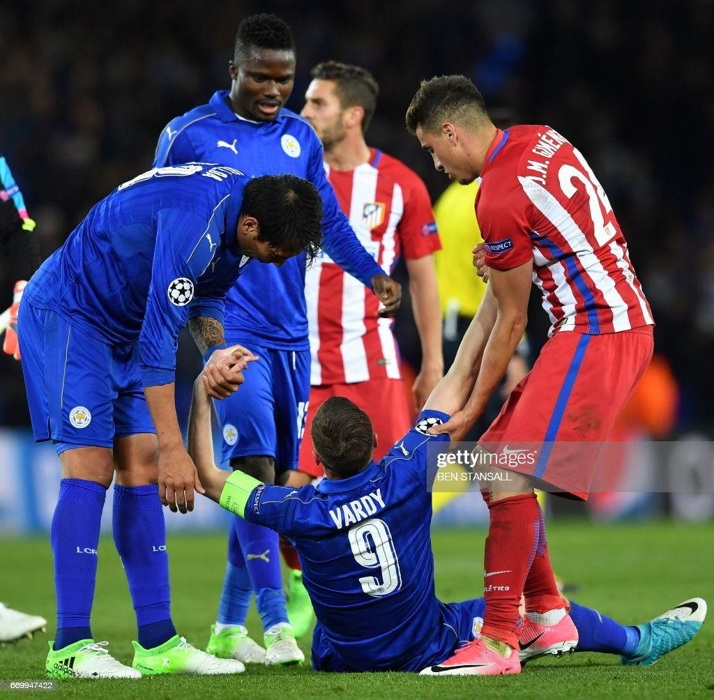 Leicester City's Argentinian striker Leonardo Ulloa (L) and Atletico Madrid's Uruguayan defender Jose Maria Gimenez (R) help a dejeceted Leicester City's English striker Jamie Vardy up following the UEFA Champions League quarter-final second leg football match between Leicester City and Club Atletico de Madrid at the King Power stadium in Leicester on April 18, 2017. The match ended in a draw at 1-1, with Atletico Madrid winning on aggregate at 2-1. / AFP PHOTO / Ben STANSALL