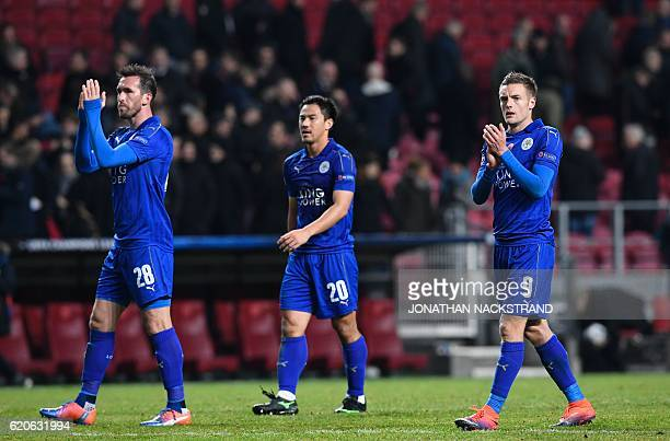 Leicester City's Austrian defender Christian Fuchs Japanese forward Shinji Okazaki and English forward Jamie Vardy react after the UEFA Champions...