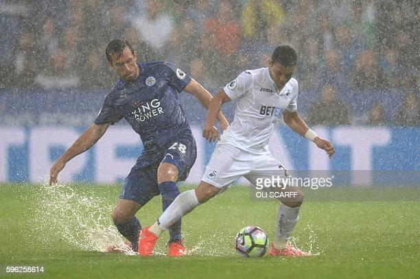 Leicester City's Austrian defender Christian Fuchs vies with Swansea City's Ecuadorian midfielder Jefferson Montero during the English Premier League...