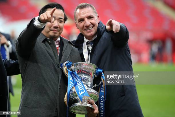 Leicester City's chairman Aiyawatt Srivaddhanaprabha and Leicester City's Northern Irish manager Brendan Rodgers hold the winner's trophy as the...