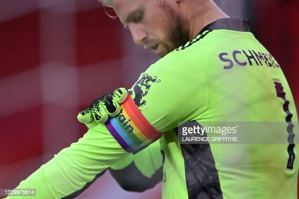 Leicester City's Danish goalkeeper Kasper Schmeichel adjusts his rainbow captains armband in support of the Stonewall Rainbow Laces during the...