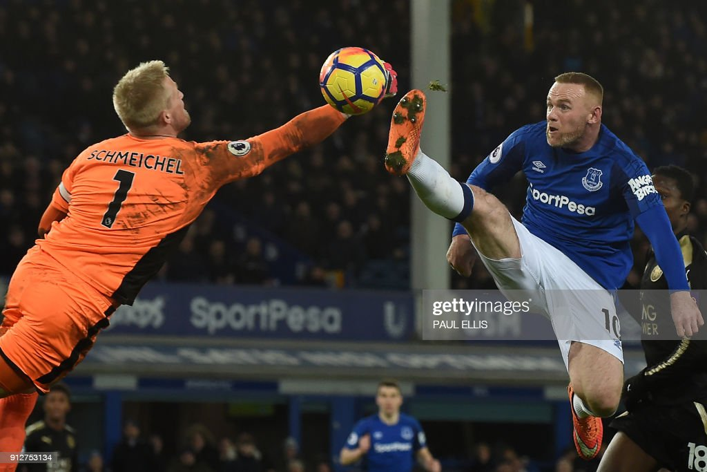 TOPSHOT - Leicester City's Danish goalkeeper Kasper Schmeichel (L) comes out to punch the ball as Everton's English striker Wayne Rooney jumps during the English Premier League football match between Everton and Leicester City at Goodison Park in Liverpool, north west England on January 31, 2018. / AFP PHOTO / PAUL ELLIS / RESTRICTED TO EDITORIAL USE. No use with unauthorized audio, video, data, fixture lists, club/league logos or 'live' services. Online in-match use limited to 75 images, no video emulation. No use in betting, games or single club/league/player publications. /