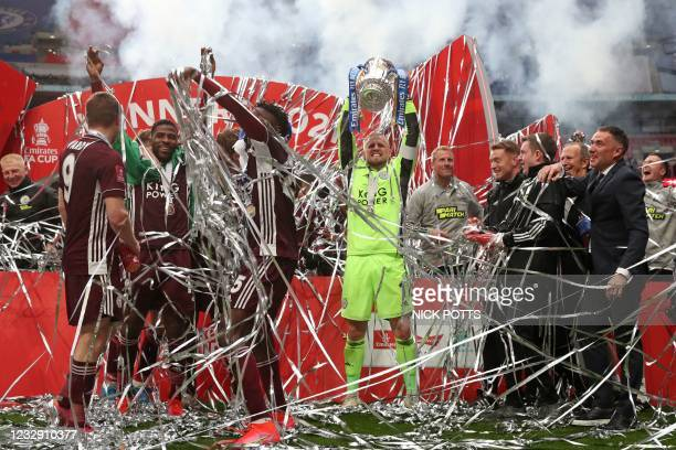 Leicester City's Danish goalkeeper Kasper Schmeichel holds up the winner's trophy as the Leicester players celebrate victory after the English FA Cup...