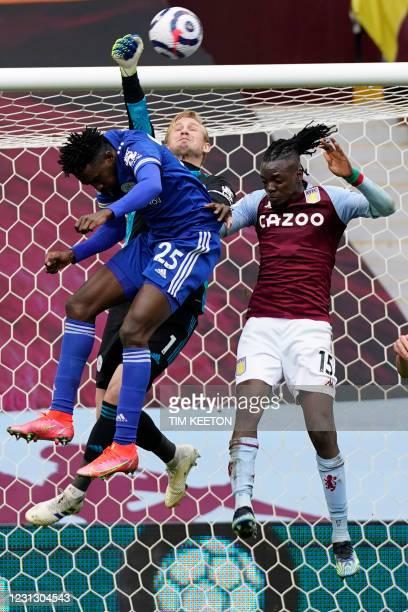 Leicester City's Danish goalkeeper Kasper Schmeichel punches the ball clear under pressure from Aston Villa's Burkinese midfielder Bertrand Traore...