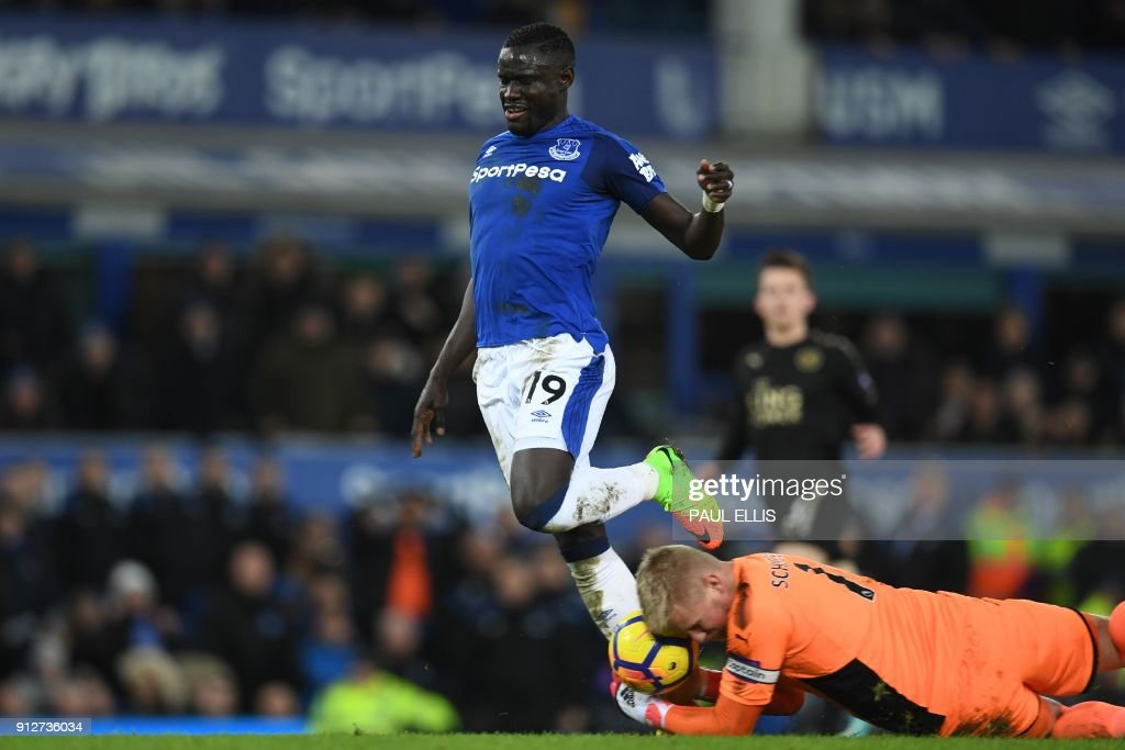 Leicester City's Danish goalkeeper Kasper Schmeichel saves at the feet of Everton's Senegalese striker Oumar Niasse during the English Premier League football match between Everton and Leicester City at Goodison Park in Liverpool, north west England on January 31, 2018. / AFP PHOTO / Paul ELLIS / RESTRICTED TO EDITORIAL USE. No use with unauthorized audio, video, data, fixture lists, club/league logos or 'live' services. Online in-match use limited to 75 images, no video emulation. No use in betting, games or single club/league/player publications. /