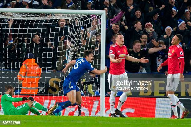 Leicester City's English defender Harry Maguire celebrates scoring their late equalizer as Manchester United's English defender Chris Smalling reacts...