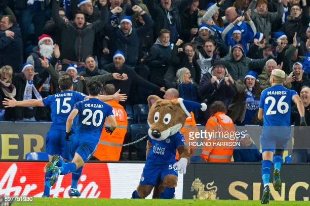 Leicester City's English defender Harry Maguire celebrates with teammates and the club mascot after scoring their late equalizer during the English...