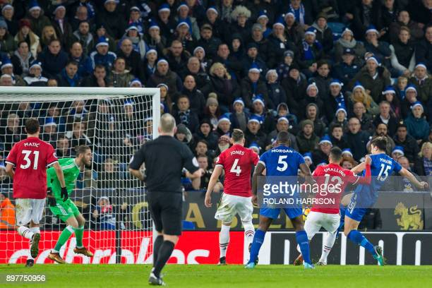 Leicester City's English defender Harry Maguire shoots to score their late equalizer during the English Premier League football match between...