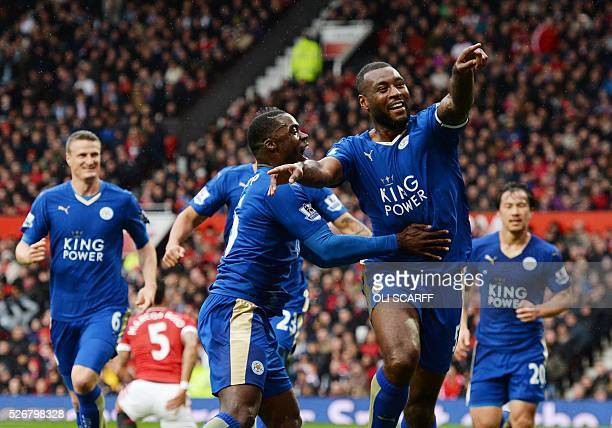 Leicester City's English defender Wes Morgan celebrates scoring the equalising 11 goal with Leicester City's Ghanaian striker Jeff Schlupp during the...