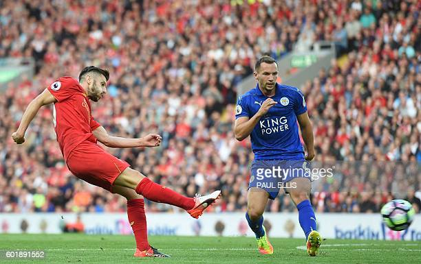 Leicester City's English midfielder Danny Drinkwater looks on as Liverpool's English midfielder Adam Lallana shoots to score their third goal during...