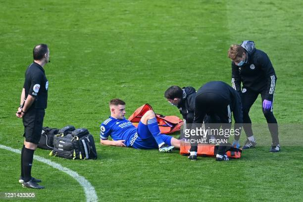 Leicester City's English midfielder Harvey Barnes is treated by medical staff after picking up an injury during the English Premier League football...