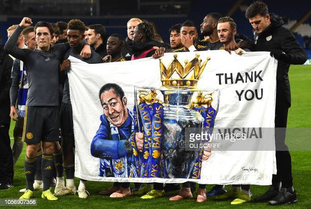 TOPSHOT Leicester City's English midfielder James Maddison and Leicester City's English midfielder Demarai Gray hold a banner showing Leicester City...