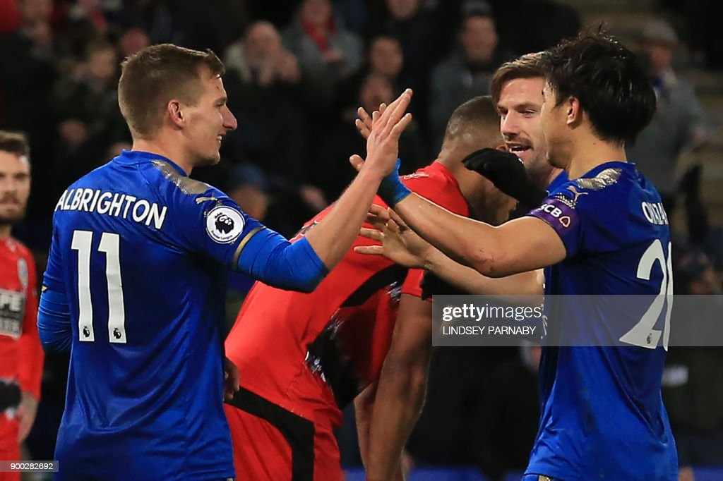 Leicester City's English midfielder Marc Albrighton (L) celebrates scoring the team's third goal, with teammates during the English Premier League football match between Leicester City and Huddersfield Town at King Power Stadium in Leicester, central England on January 1, 2018. / AFP PHOTO / Lindsey PARNABY / RESTRICTED TO EDITORIAL USE. No use with unauthorized audio, video, data, fixture lists, club/league logos or 'live' services. Online in-match use limited to 75 images, no video emulation. No use in betting, games or single club/league/player publications. /