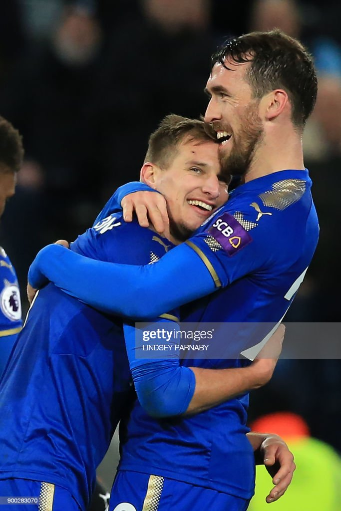 Leicester City's English midfielder Marc Albrighton (L) celebrates scoring the team's third goal with Leicester City's Austrian defender Christian Fuchs during the English Premier League football match between Leicester City and Huddersfield Town at King Power Stadium in Leicester, central England on January 1, 2018. / AFP PHOTO / Lindsey PARNABY / RESTRICTED TO EDITORIAL USE. No use with unauthorized audio, video, data, fixture lists, club/league logos or 'live' services. Online in-match use limited to 75 images, no video emulation. No use in betting, games or single club/league/player publications. /