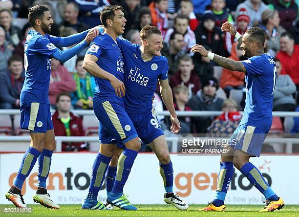 Leicester City's English striker Jamie Vardy celebrates scoring his team's first goal with Leicester City's Argentinian striker Leonardo Ulloa and...