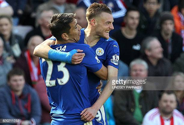 Leicester City's English striker Jamie Vardy celebrates scoring his team's first goal with Leicester City's Argentinian striker Leonardo Ulloa during...
