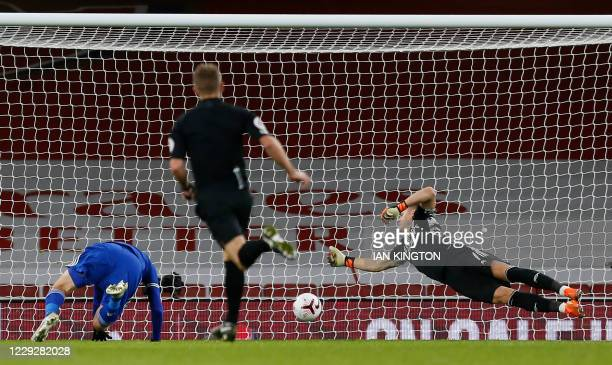 Leicester City's English striker Jamie Vardy headers the opening goal past Arsenal's German goalkeeper Bernd Leno during the English Premier League...