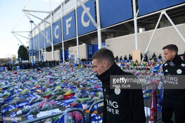Leicester City's English striker Jamie Vardy looks at the floral tributes left to the victims of the helicopter crash which killed Leicester City's...