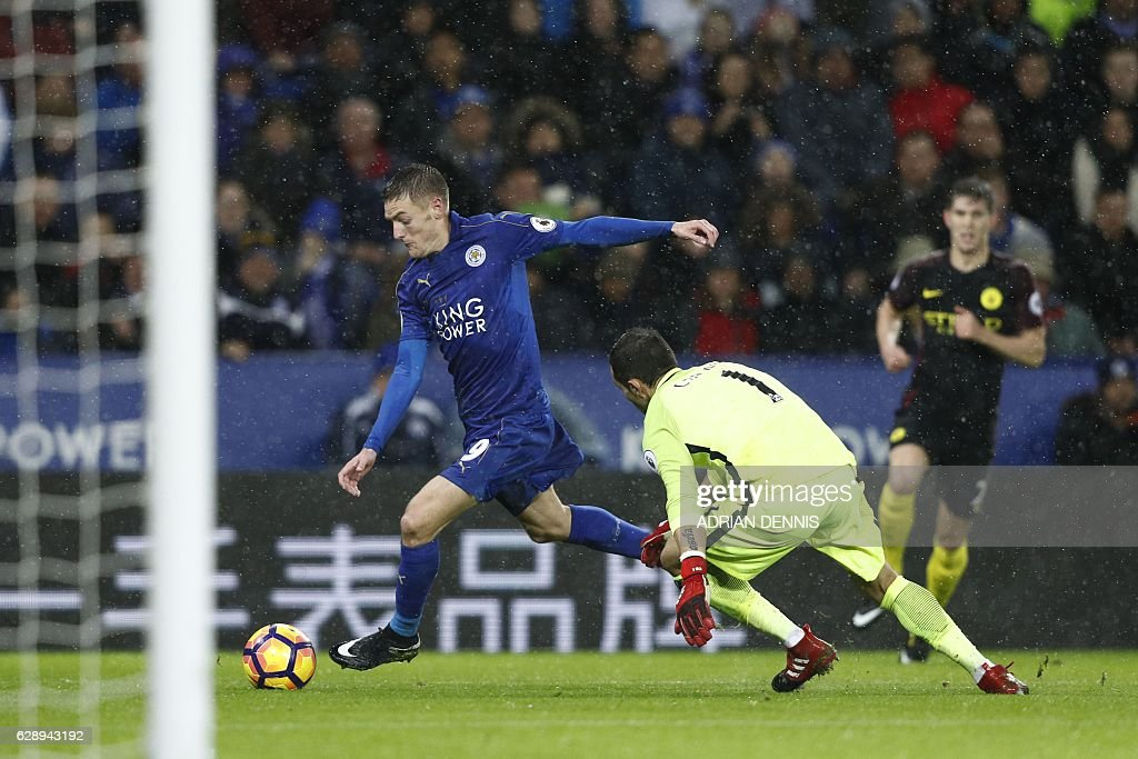 Leicester City's English striker Jamie Vardy (L) takes the ball around Manchester City's Chilean goalkeeper Claudio Bravo on his way to scoring his third goal, their fourth during the English Premier League football match between Leicester City and Manchester City at King Power Stadium in Leicester, central England on December 10, 2016. / AFP / Adrian DENNIS / RESTRICTED TO EDITORIAL USE. No use with unauthorized audio, video, data, fixture lists, club/league logos or 'live' services. Online in-match use limited to 75 images, no video emulation. No use in betting, games or single club/league/player publications. /