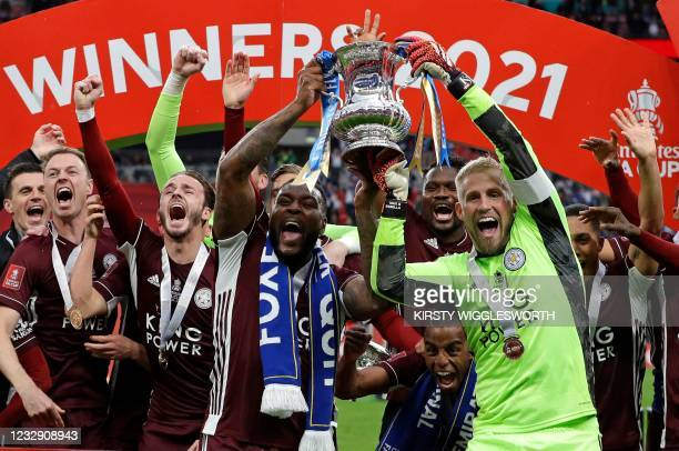 Leicester City's English-born Jamaican defender Wes Morgan and Leicester City's Danish goalkeeper Kasper Schmeichel hold up the winner's trophy as...