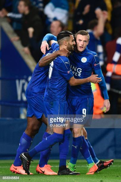 Leicester City's Englishborn Jamaican defender Wes Morgan celebrates after scoring the opening goal with teammates Leicester City's Algerian...