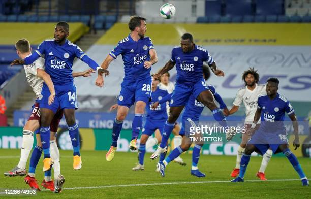 Leicester City's English-born Jamaican defender Wes Morgan headers the ball clear from a corner kick during the English League Cup third round...