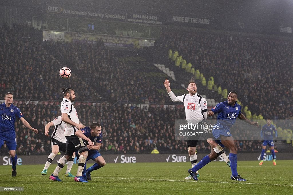 Leicester City's English-born Jamaican defender Wes Morgan heads the ball past Derby's English-born Irish defender Richard Keogh to score their second goal during the English FA Cup fourth round football match between Derby County and Leicester City at Pride Park Stadium in Derby, central England on January 27, 2017. / AFP / Oli SCARFF / RESTRICTED TO EDITORIAL USE. No use with unauthorized audio, video, data, fixture lists, club/league logos or 'live' services. Online in-match use limited to 75 images, no video emulation. No use in betting, games or single club/league/player publications. /