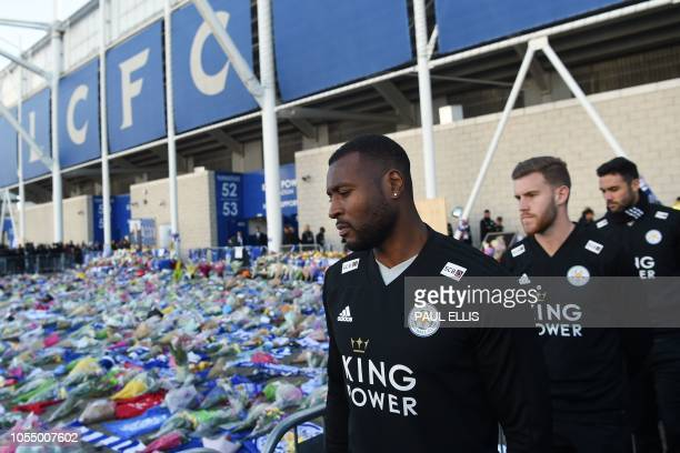 TOPSHOT Leicester City's Englishborn Jamaican defender Wes Morgan looks at the floral tributes left to the victims of the helicopter crash which...
