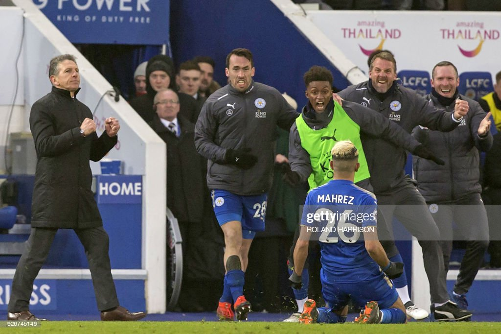 Leicester City's French manager Claude Puel (L) reacts as Leicester City's Algerian midfielder Riyad Mahrez (C) celebrates scoring his late goal with teammates and staff during the English Premier League football match between Leicester City and Bournemouth at King Power Stadium in Leicester, central England on March 3, 2018. The game finished 1-1. / AFP PHOTO / Roland HARRISON / RESTRICTED TO EDITORIAL USE. No use with unauthorized audio, video, data, fixture lists, club/league logos or 'live' services. Online in-match use limited to 75 images, no video emulation. No use in betting, games or single club/league/player publications. /