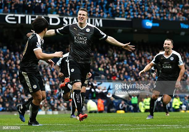 Leicester City's German defender Robert Huth celebrates scoring his team's third goal with Leicester City's Japanese striker Shinji Okazaki during...