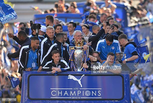 Leicester City's Italian manager Claudio Ranieri stands with the Premier league trophy as the Leicester City team take part in an opentop bus parade...