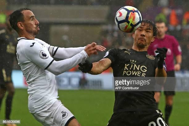 Leicester City's Japanese striker Shinji Okazaki vies with Swansea City's English midfielder Leon Britton during the English Premier League football...