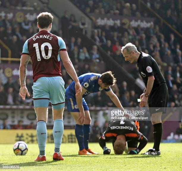 Leicester City's Kasper Schmeichel is injured by Burnley's Ashley Barnes who was shown a yellow card by Referee Martin Atkinson for the challenge...