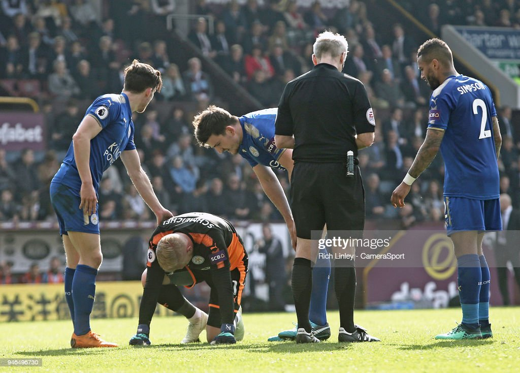 Leicester City's Kasper Schmeichel is injured by Burnley's Ashley Barnes who was shown a yellow card by Referee Martin Atkinson for the challenge during the Premier League match between Burnley and Leicester City at Turf Moor on April 14, 2018 in Burnley, England.