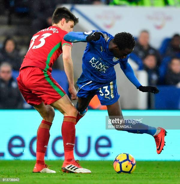 Leicester City's Malian midfielder Fousseni Diabate goes down in a challenge with Swansea City's Argentinian defender Federico Fernandez during the...