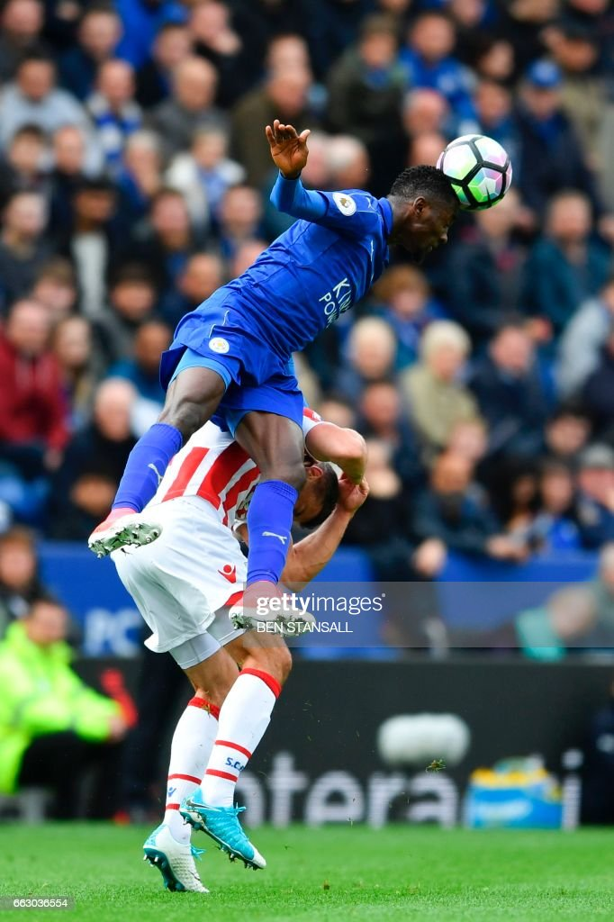 Leicester City's Nigerian midfielder Wilfred Ndidi (C) beats Stoke City's English-born Irish striker Jonathan Walters to head the ball during the English Premier League football match between Leicester City and Stoke City at King Power Stadium in Leicester, central England on April 1, 2017. / AFP PHOTO / Ben STANSALL / RESTRICTED TO EDITORIAL USE. No use with unauthorized audio, video, data, fixture lists, club/league logos or 'live' services. Online in-match use limited to 75 images, no video emulation. No use in betting, games or single club/league/player publications. /