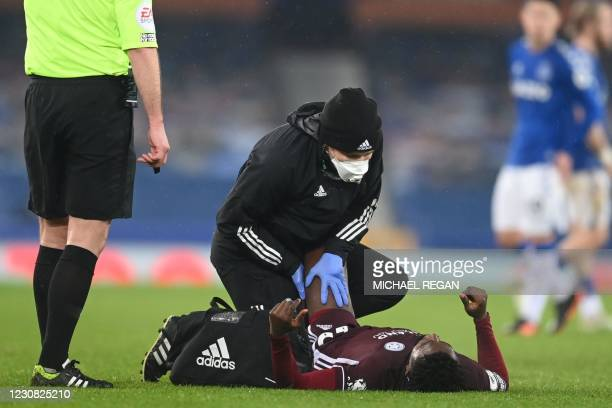 Leicester City's Nigerian midfielder Wilfred Ndidi receives medical attention during the English Premier League football match between Everton and...