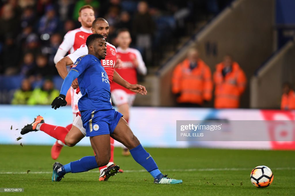 Leicester City's Nigerian striker Kelechi Iheanacho (C) scores the team's first goal past Fleetwood Town's English goalkeeper Chris Neal during the English FA Cup third round replay football match between Leicester City and Fleetwood Town at King Power Stadium in Leicester, central England on January 16, 2018. / AFP PHOTO / Paul ELLIS / RESTRICTED TO EDITORIAL USE. No use with unauthorized audio, video, data, fixture lists, club/league logos or 'live' services. Online in-match use limited to 75 images, no video emulation. No use in betting, games or single club/league/player publications. /
