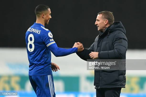 Leicester City's Northern Irish manager Brendan Rodgers shakes hands with Leicester City's Belgian midfielder Youri Tielemans after the English...
