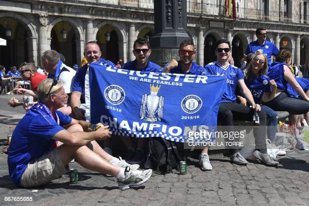 Leicester City's supporters pose with team flag on Plaza Mayor before the UEFA Champions League quarter final first leg football match Club Atletico...