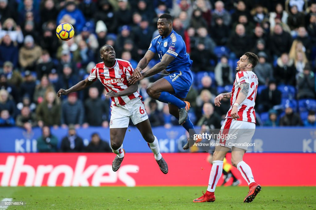 Leicester City's Wes Morgan heads at goal under pressure from Stoke City's Kurt Zouma as Stoke City's Geoff Cameron looks on during the Premier League match between Leicester City and Stoke City at The King Power Stadium on February 24, 2018 in Leicester, England.
