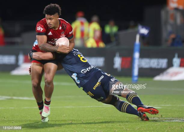 Leicester Fainga'anuku of the Crusaders is tackled by Kazuki Himenoof the Highlanders during the round 6 Super Rugby Aotearoa match between the...