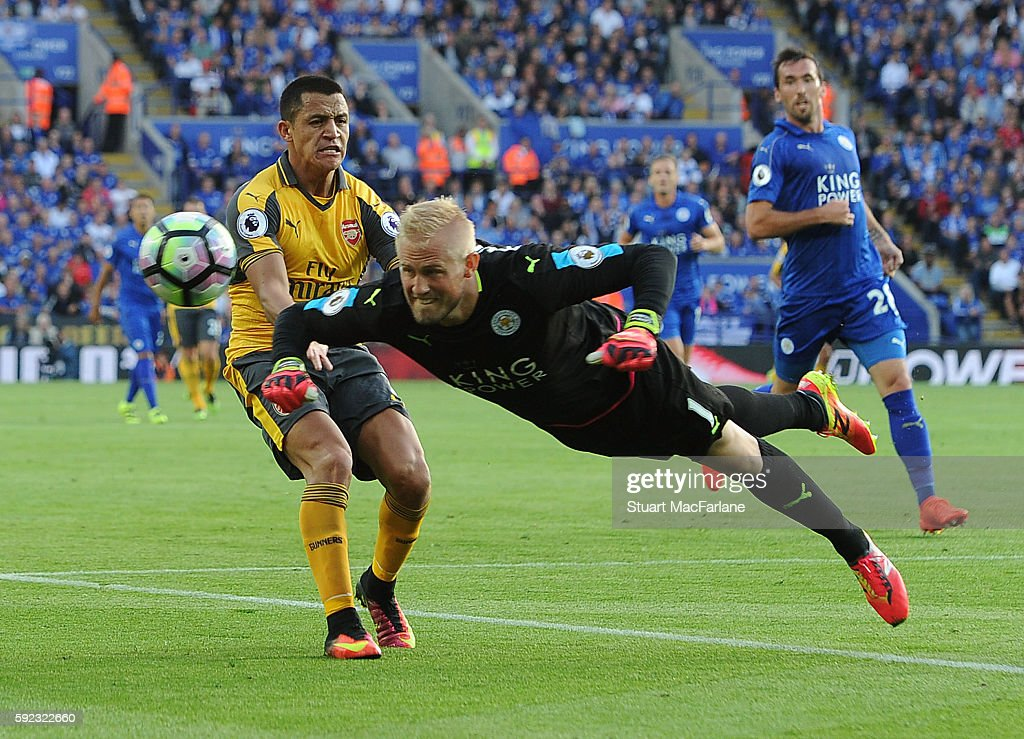 Leicester goalkeeper Kasper Schmeichel heads clear from Arsenal's Alexis Sanchez during the Premier League match between Leicester City and Arsenal at The King Power Stadium on August 20, 2016 in Leicester, England.