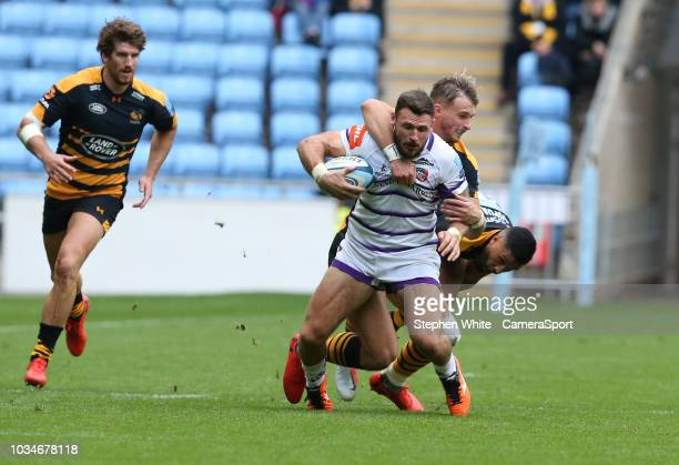 Leicester Tigers' Adam Thompstone is tackled by Wasps' Lima Sopoaga and Josh Bassett during the Gallagher Premiership Rugby match between Wasps and...