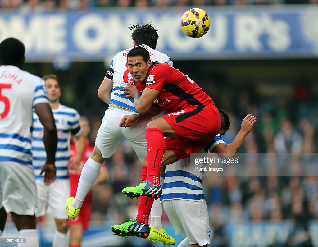 Leicester's Leo Ulloa battles with QPR's Joey Barton during the Barclays premier League match between Queens Park Rangers and Leicester City at Loftus Road on November 29, 2014 in London, England.