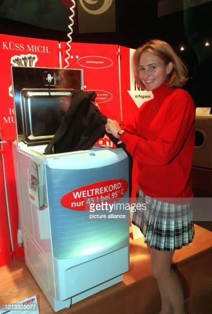 Leichtathletin Kerstin Fuhrmann legt einen Pullover in eine neuentwickelte Waschmaschine die am 7296 in Berlin vorgestellt wird Das Gerät ist mit...