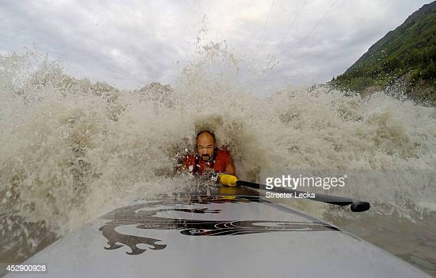 Leif Ramos holds onto his board and paddle as he catches the lead wave of the Bore Tide at Turnagain Arm on July 15 2014 in Anchorage Alaska Alaska's...