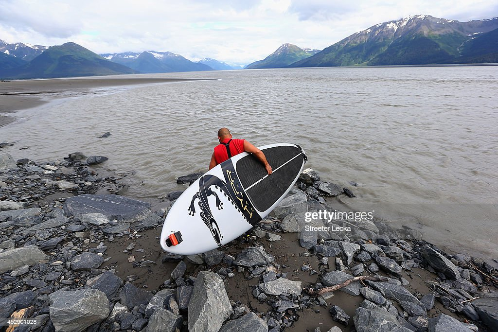 Leif Ramos puts in at his usual spot along the Seward highway as he prepares to surf the Bore Tide at Turnagain Arm on July 13, 2014 in Anchorage, Alaska. Alaska's most famous Bore Tide, occurs in a spot on the outside of Anchorage in the lower arm of the Cook Inlet, Turnagain Arm, where wave heights can reach 6-10 feet tall, move at 10-15 mph and the water temperature stays around 40 degrees Fahrenheit. This years Supermoon substantially increased the size of the normal wave and made it a destination for surfers.