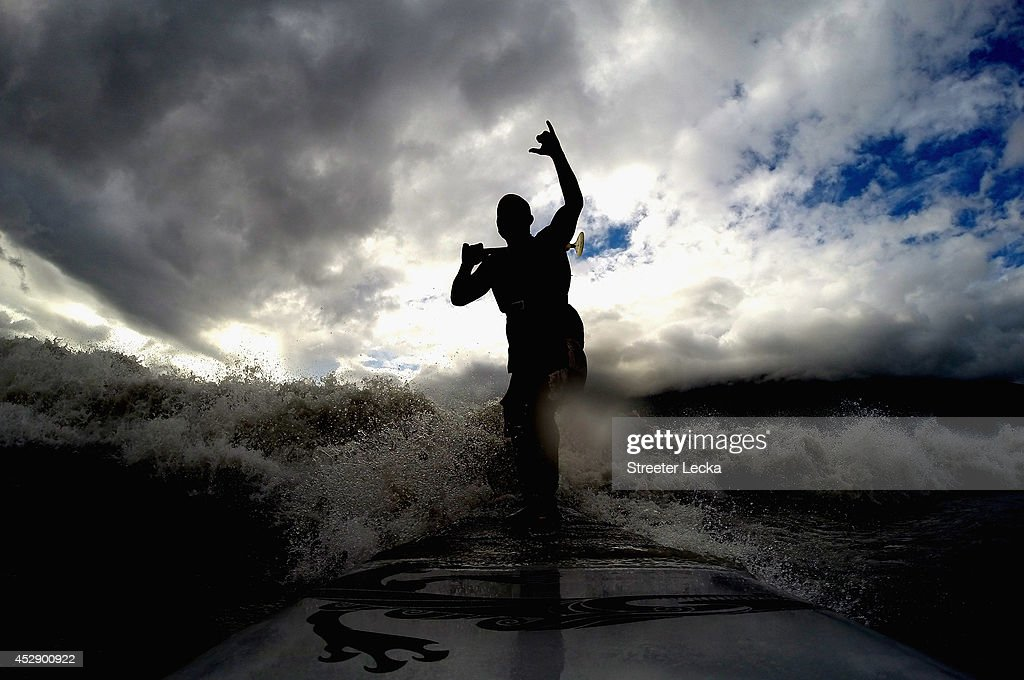 Leif Ramos signals with his hand as he catches and rides the Bore Tide at Turnagain Arm on July 13, 2014 in Anchorage, Alaska. Alaska's most famous Bore Tide, occurs in a spot on the outside of Anchorage in the lower arm of the Cook Inlet, Turnagain Arm, where wave heights can reach 6-10 feet tall, move at 10-15 mph and the water temperature stays around 40 degrees Fahrenheit. This years Supermoon substantially increased the size of the normal wave and made it a destination for surfers.